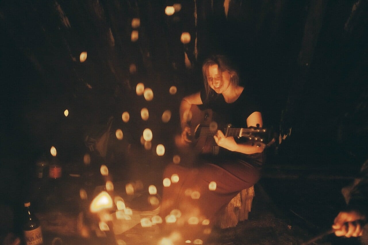 Campfire and Guitar being played by a woman