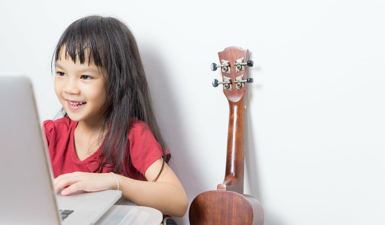 Young girl musician is taking music class online.